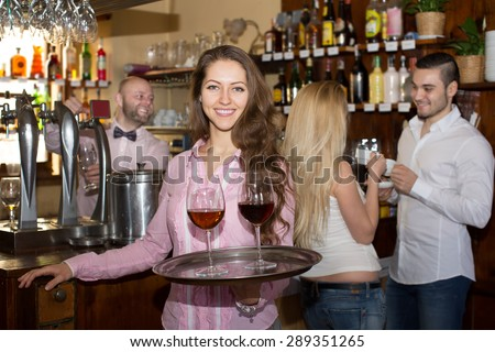 Smiling nippy serving bar guests with beverages