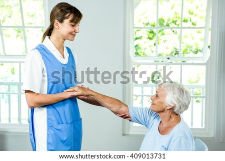 Smiling nurse assisting active senior at health club