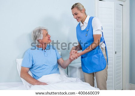 Smiling nurse holding senior man hand in hospital