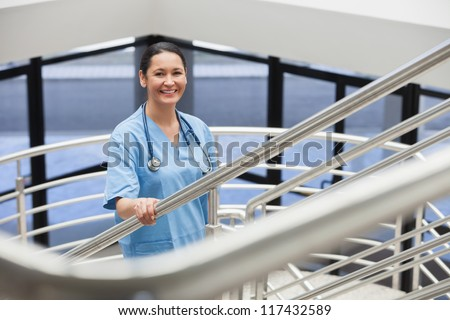 Smiling nurse in a stairwell in hospital corridor - stock photo