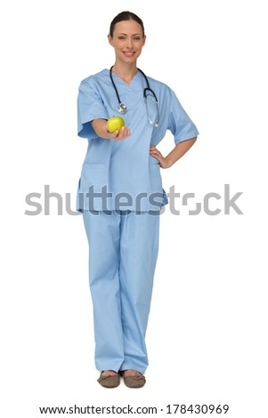 Smiling nurse in scrubs holding green apple on white background - stock photo