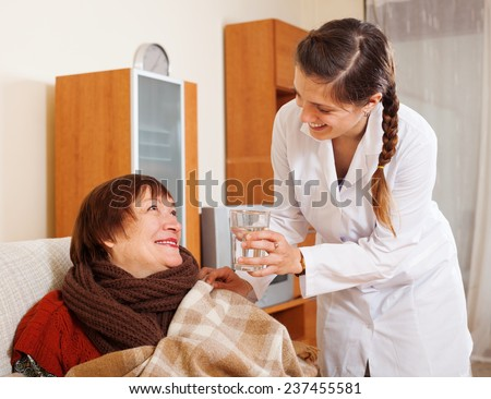 Smiling nurse in uniform caring for happy mature woman in living room at home - stock photo