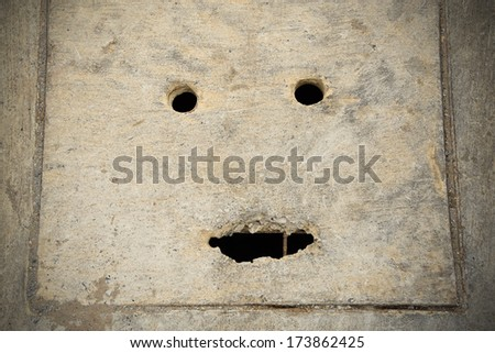 Smiling of concret sewer cover - stock photo