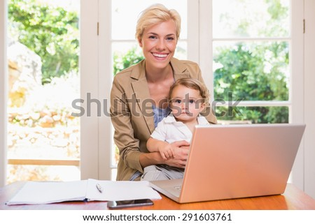 Smiling of pretty blonde woman with his son using laptop in the office - stock photo