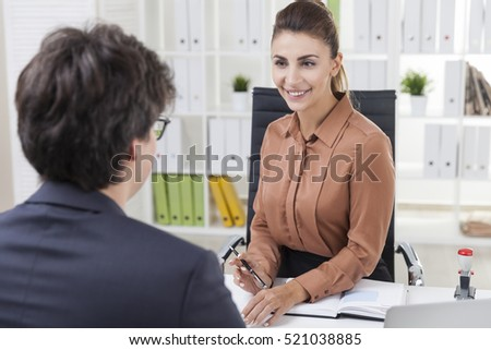 Smiling office employee is sitting at her table and looking at a businessman wearing glasses. Overt the shoulder shot.