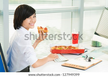 Smiling office lady working at lunchtime and eating pepperoni - stock photo