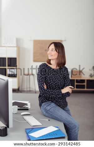 Smiling Office Woman Sitting on her Worktable with Arms Crossing In Front her Body, Looking Into Distance While Thinking of Something. - stock photo