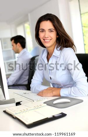 Smiling office worker in front of desktop computer - stock photo