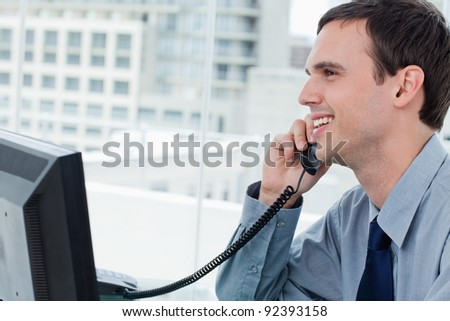 Smiling office worker on the phone in his office - stock photo