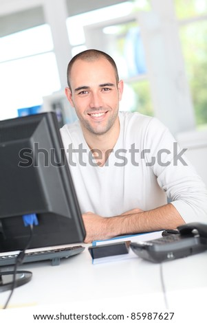 Smiling office worker sitting in front of desktop computer - stock photo