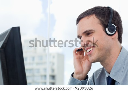 Smiling office worker using a headset in his office - stock photo