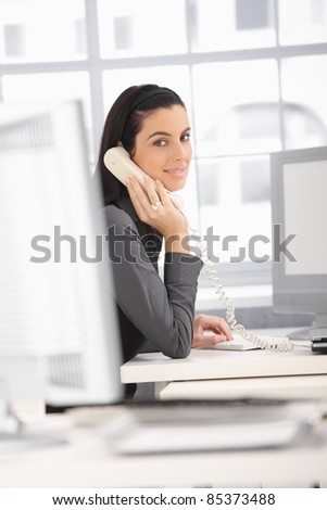Smiling office worker woman sitting at desk on landline phone call, looking at camera.?