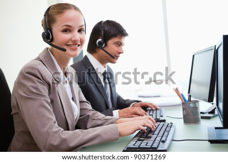 Smiling office workers using computers in an office - stock photo