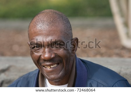 Smiling old African American man outside during the daytime - stock photo
