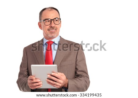 smiling old businessman holding tablet pad computer looks to his side on white background