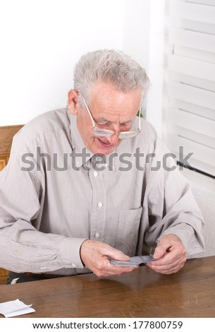 Smiling old man counting cards in game