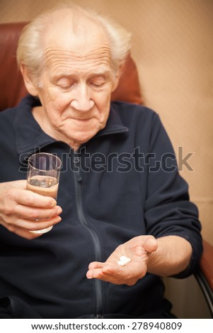 Smiling old man holding a glass of water and a mix of pills. Focus is on his hands - stock photo