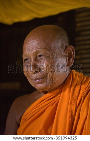 Smiling old monk. Teacher - Monk, the superintendent of one of the Buddhist temples, looking thoughtfully toward the temple. His face wrinkled old times. November 30 2009: Monastery. Phnom Penh