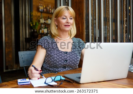 Smiling old senior blonde business woman 60-65 years, alone with laptop in summer cafe