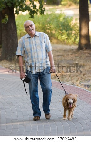 Smiling old senior relaxing in park, and having fun with his dog. - stock photo
