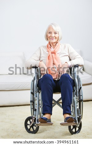 Smiling old senior woman in wheelchair at home - stock photo