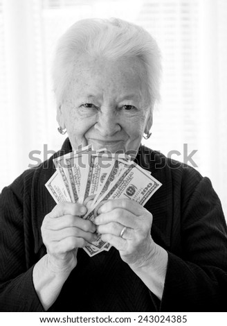 Smiling old woman holding money in hands on a white background - stock photo