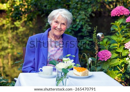 Smiling Old Woman in Blue Violet Blazer Sitting at the Garden Table with Coffee and Cake, Smiling at the Camera. - stock photo