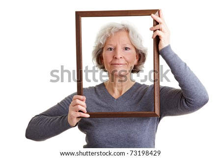 Smiling old woman looking through an empty frame
