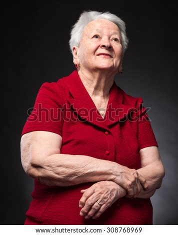 Smiling old woman looking up on a dark background - stock photo