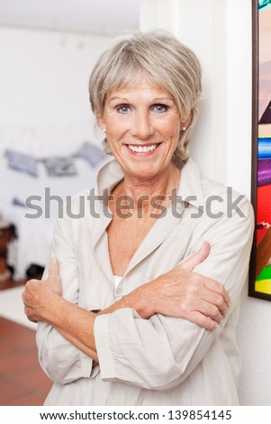Smiling old woman posing with arms crossed - stock photo