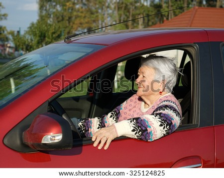 Smiling old woman sitting inside the car - stock photo