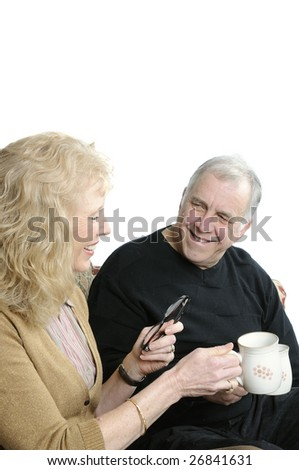 Smiling older couple enjoying coffee or tea sitting on sofa, isolated over white - stock photo