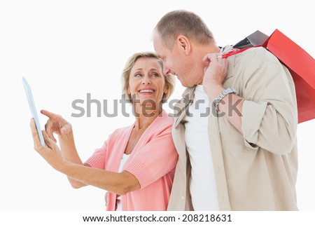 Smiling older couple holding shopping bags looking at tablet pc on white background - stock photo