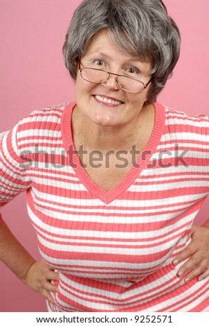 Smiling older woman in glasses on pink background - stock photo