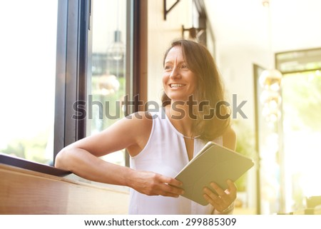 Smiling older woman with tablet looking away - stock photo