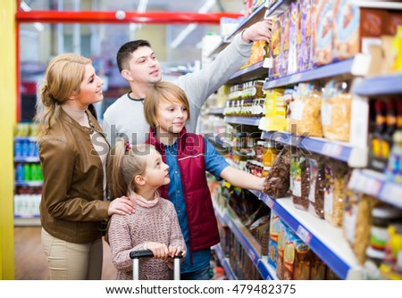 Smiling ordinary family with children choosing cereal for breakfast in supermarket. Selective focus