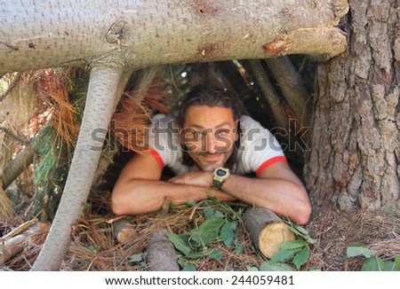 smiling out of focus man in the wild under a shelter - stock photo