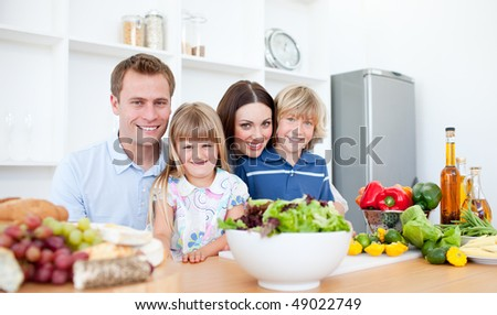 Smiling parents and their children preparing dinner together in the kitchen