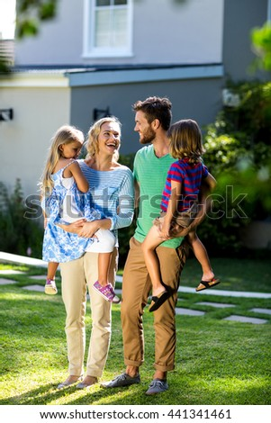 Smiling parents carrying children in yard against house - stock photo