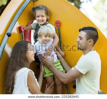 Smiling parents helping children on stairs at park  - stock photo