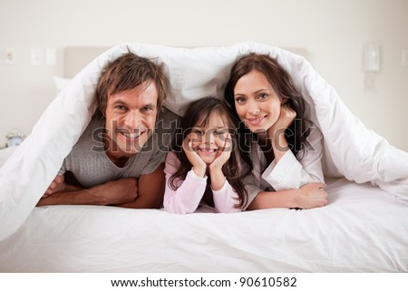 Smiling parents lying under a duvet with their daughter in their bedroom - stock photo