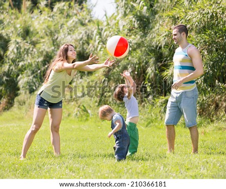 Smiling parents with children playing in park at sunny day - stock photo