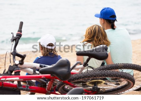 Smiling parents with kid having rest after cycling on the beach - stock photo