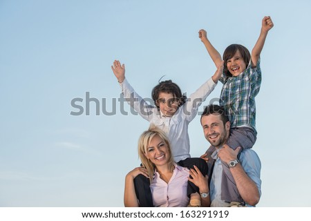 Smiling parents with playful kids outdoors - stock photo