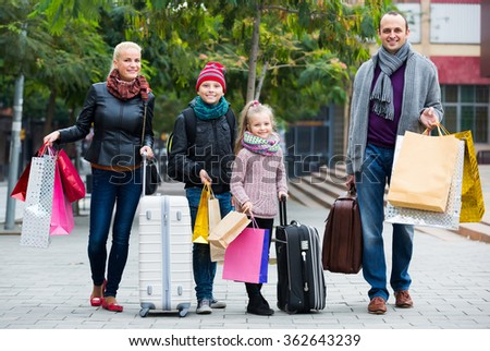 Smiling parents with school age children enjoying shopping tour