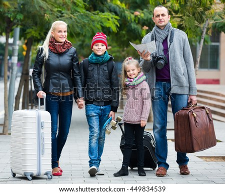 Smiling parents with two kids and baggage using urban map