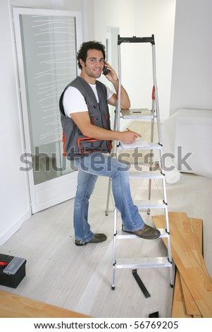 Smiling parquet layer on phone leaning on a ladder - stock photo