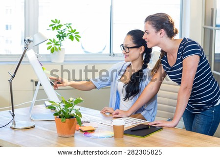 Smiling partners working together with photographs on computer in the office - stock photo