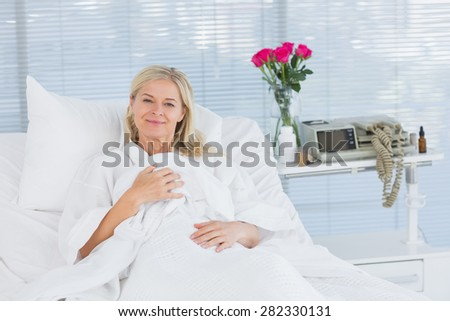 Smiling patient looking at camera on her bed in hospital - stock photo