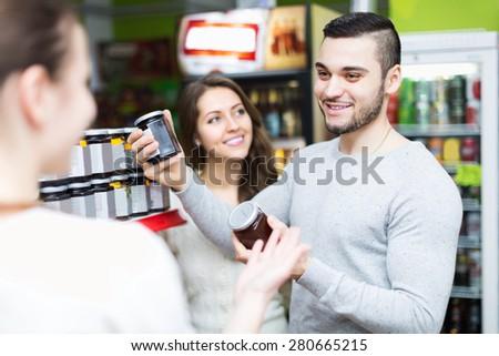 Smiling people choosing tinned food at supermarket - stock photo
